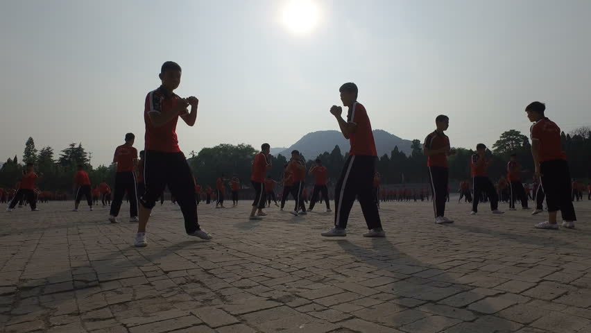 SHAOLIN, CHINA - MAY 2016: Silhouettes of martial arts students boxing (as part of a training session) at the grounds of the Shaolin Kung Fu institute in central China