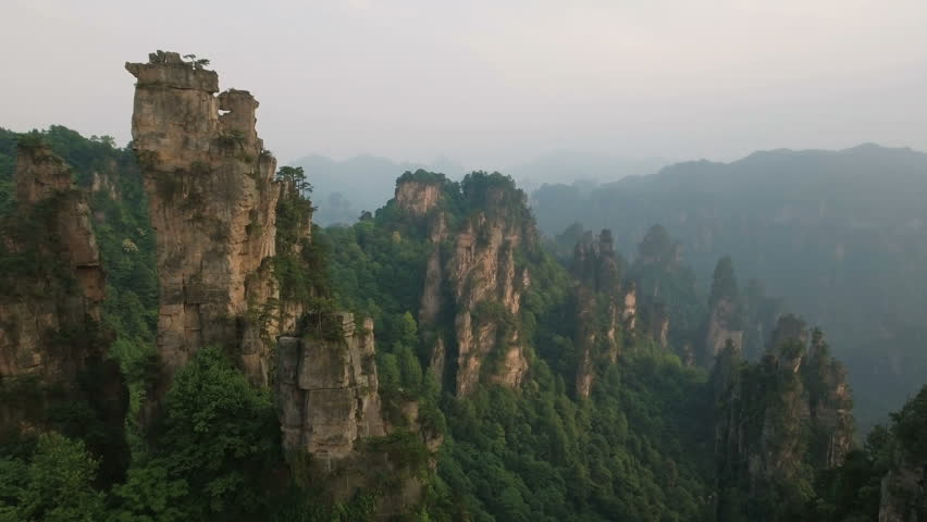 Beautiful aerial view flying a drone through the spectacular mountain landscape of Zhangjiajie, a national park in China known for its surreal scenery of rock formations.