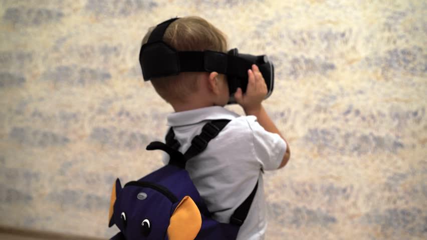 Little boy use virtual reality headset helmet. VR. Virtual reality. 4K resolution. New technology. Hi-tech. High technology. Virtual reality glasses.    Shutterstock HD Video #19924315