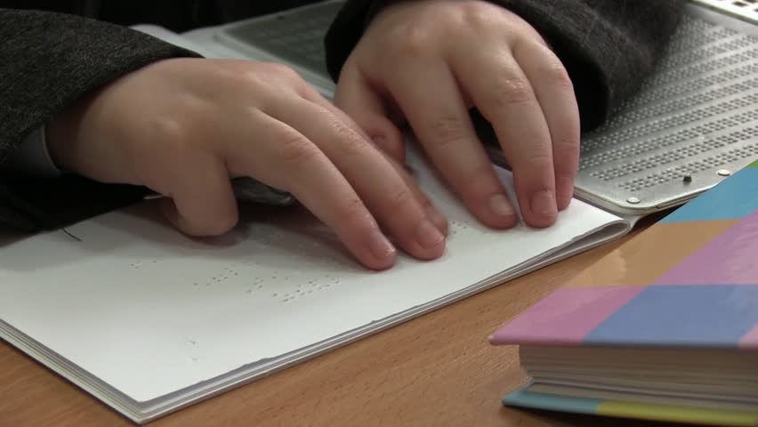 Kid Reading Braille. The child learns to read Braille on a sheet of paper sitting at the desk in the school