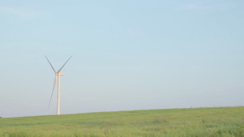 Looking across a field at a wind turbine turning, generating electricity. Blue sky background. Space for copy.
