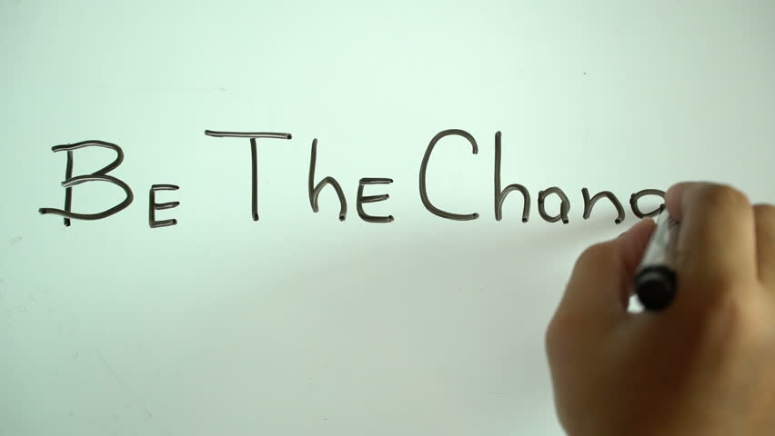 "Hand writing title ""Be the change"" using a black marker on a white board"