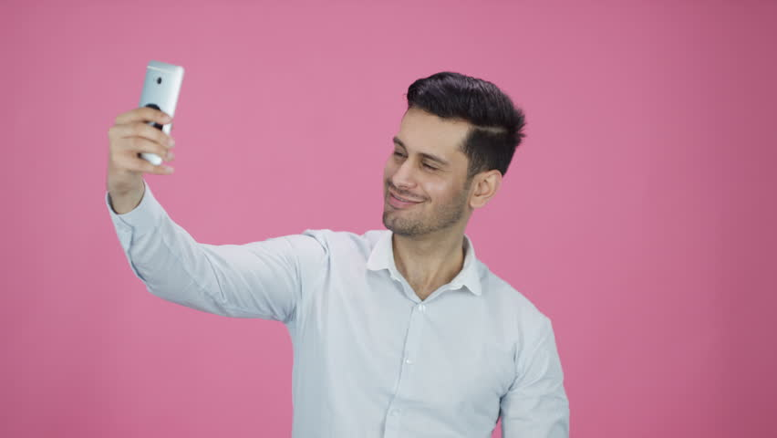 Young Asian male on pink background looking at cell phone technology | Shutterstock HD Video #19990525