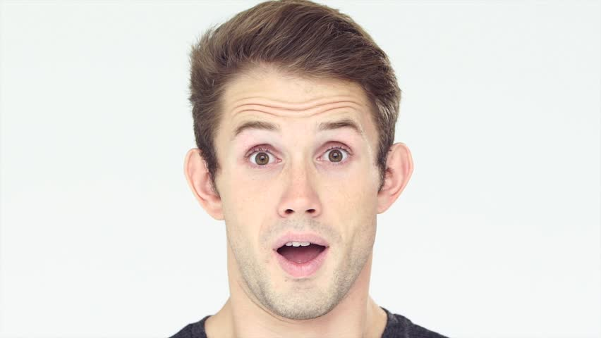 Closeup portrait of young handsome man face expressing astonishment and admiration in studio on white background. Slow motion