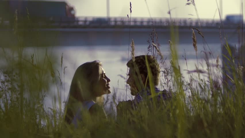 Young couple kissing romantically while relaxing in tall grass