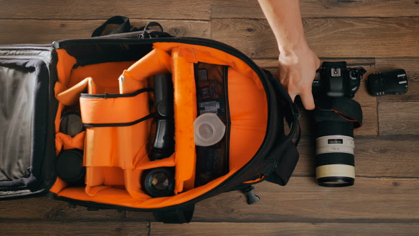 Photographer pack his camera and lenses to bagpack. Bag and appliances for photography top view. Tourist with digital cameras.