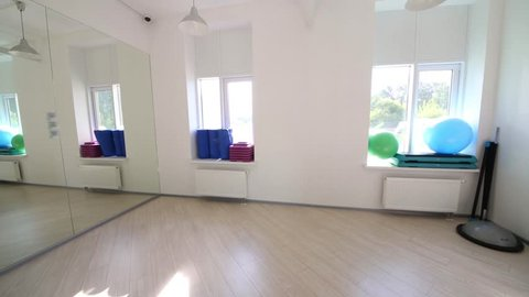 Empty gym with balls, dumbbells and mats on the windowsills and shelves
