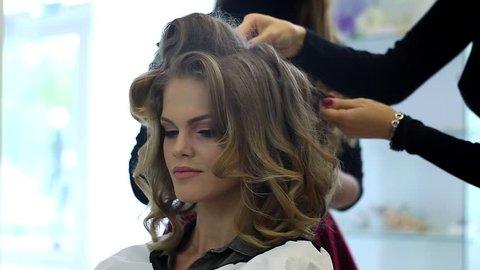 Hairdresser makes hairdress beautiful girl in a beauty salon
