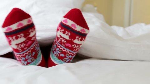 Female legs in christmas socks in bed  dolly shot