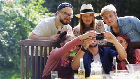 leisure, party, technology, people and holidays concept - happy friends taking selfie with smartphone and gathering for dinner at summer garden party