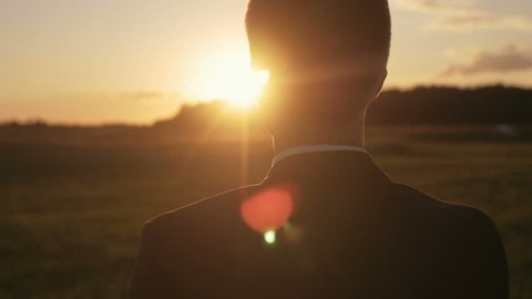 Young man looking forward at the sun during the sunrise. Businessman thinking about business planning.