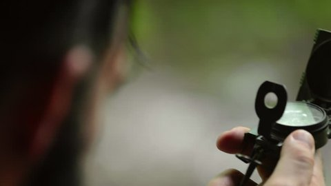 A man uses a magnetic navigational compass and map. Shallow focus.