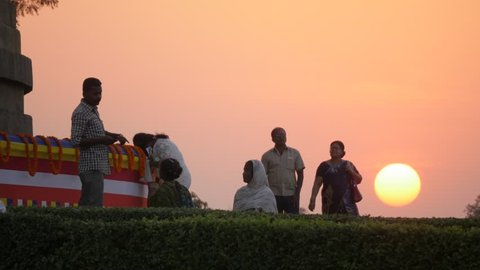 Sarnath, India - February 25,2016: Pilgrims walking around Dhamekh Stupa at sunset