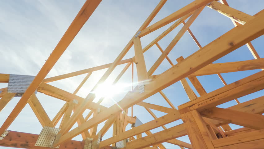 Roof beams of a modern American home in mid construction phase, looking up toward blue sky with sunlight | Shutterstock HD Video #20181772