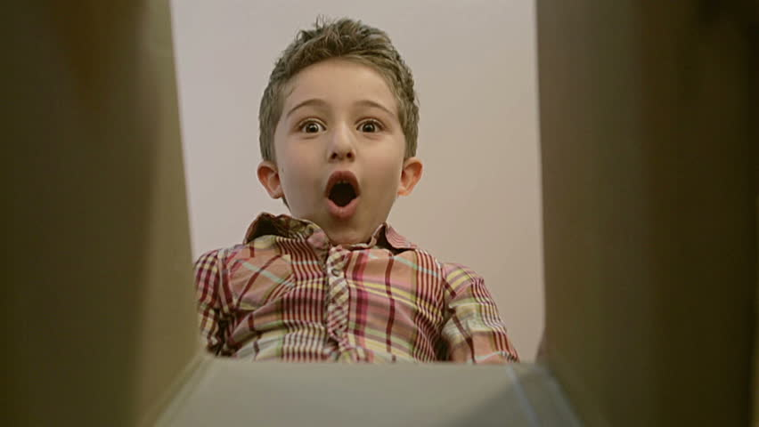 Little boy opens a parcel box with different versions of emotions and being surprised.