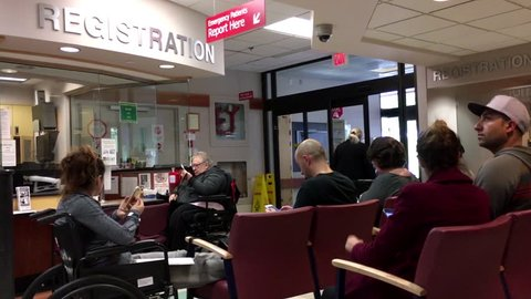 Port Moody, BC, Canada - October 03, 2016 : People sitting in a hospital emergency registration area.