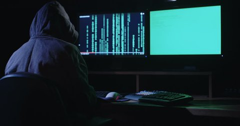 Computer hacker sitting in a dark room in front of computer screens hacking and writing lines of code