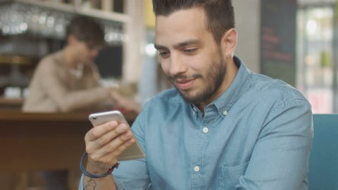 Hispanic Ethnicity Young Man using Mobile Phone at Cozy Coffee Shop. Shot on RED Cinema Camera in 4K (UHD).