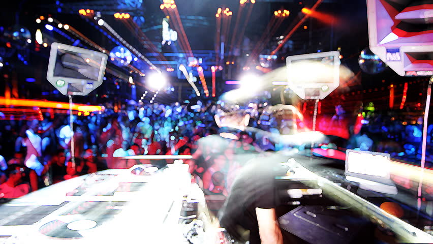 shot of dj playing from behind looking out to the crowd in privilege club, ibiza, spain