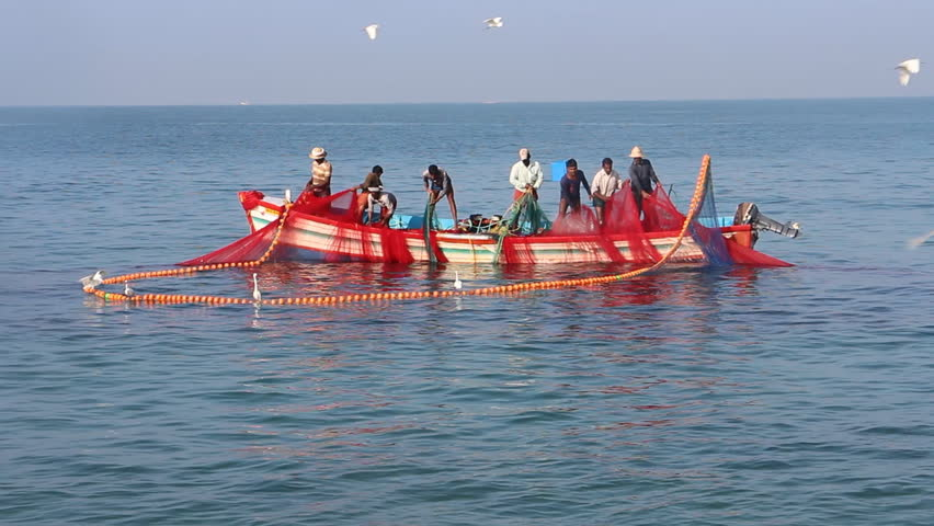 India, Kerala - December 27, 2015: Indian fishermen graphically get painted seine right in boat 2. Net bright colors, white herons grabbing fish, flying terns, wooden beautiful boat. Heard Hindu hymns
