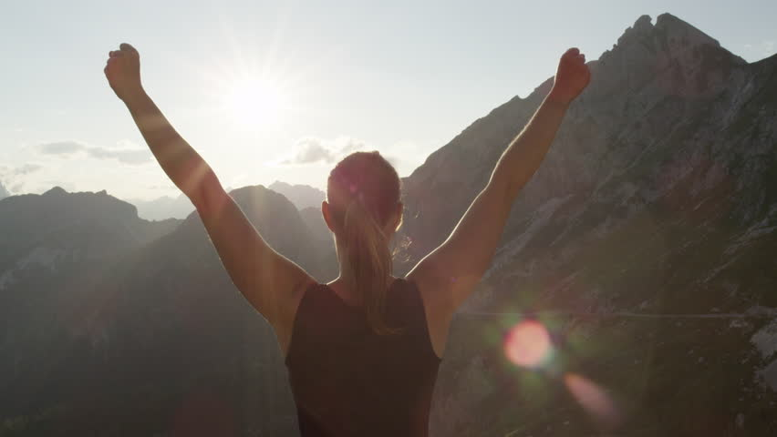 SLOW MOTION, CLOSE UP: Young woman standing on the edge of the cliff and raising her hands up against high rocky mountains sunbathing in evening sun. Happy girl enjoying success and stunning view