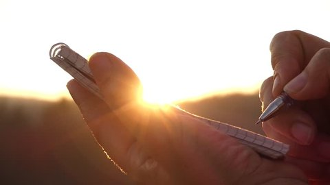 the Girl's Hand Making Notes in a Notebook at Sunset in Rays of the Sun. Beautiful Action.