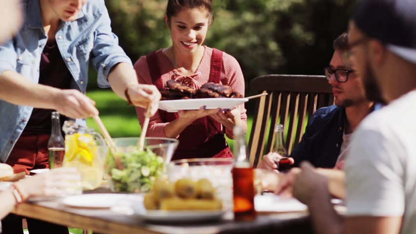 Leisure, holidays, eating, people and food concept - happy friends having dinner at summer garden party | Shutterstock HD Video #20265922