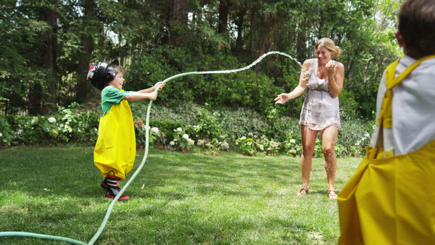 A young boy dressed in homemade fireman gear spraying his mother with a garden hose while his brother - also in costume - watches. Slow motion.