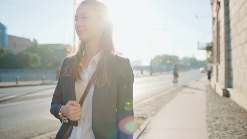 Young Businesswoman Going to Work in the Sunny Morning City. SLOW MOTION. STEADICAM Stabilized Shot. Attractive Professional Business Woman with Tablet rushing to a morning meeting. Lens Flare.