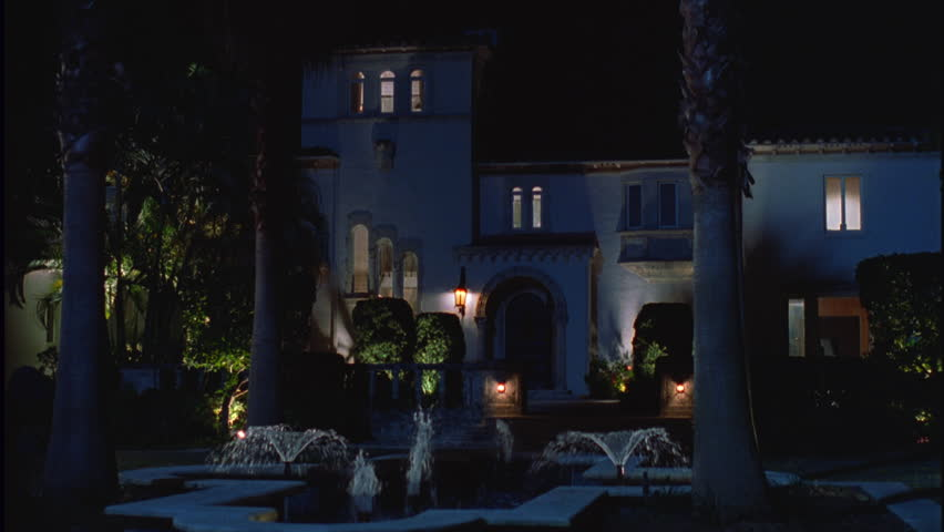night Across yard, fountain palms 3 story very upscale Spanish Mediterranean style house an arched door entry mansion hotel country club Santa Barbara bed Breakfast, etc