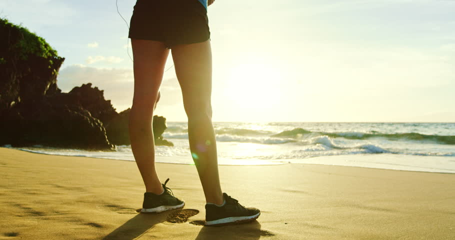 Athletic young woman putting in headphones before sunset run on the beach #20348605