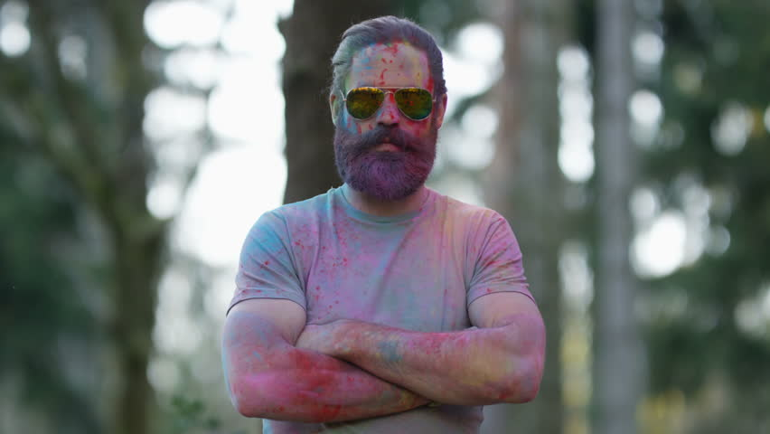 4K Portrait of serious hipster guy standing still while being covered in coloured powder at festival. Shot on RED Epic.
