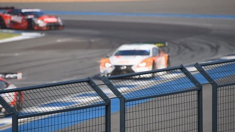 Shot of a fenced in race car cercuit, with the focus on the fence