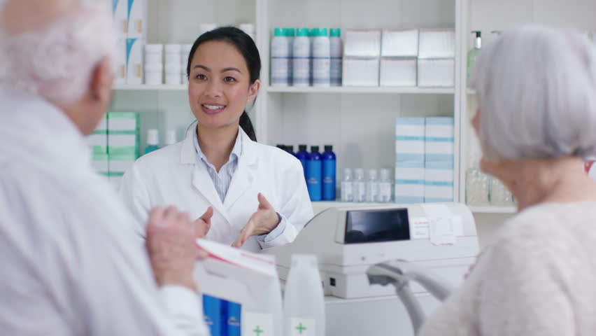 4K Friendly pharmacy worker serving senior couple & taking payment at the till. Shot on RED Epic. | Shutterstock HD Video #20382745