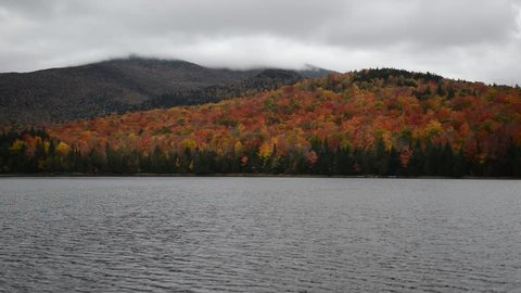 Vibrant Autumn foliage with red, orange and yellow fall colors in A Northeast forest with lake and clouds