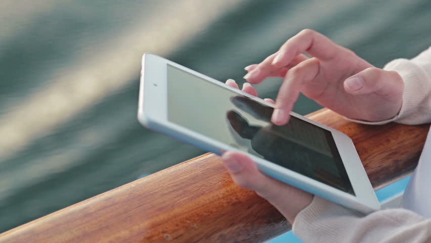Woman Using Tablet On Deck Of Cruise Ship Scrolling And Touching - How to use cell phone on cruise ship