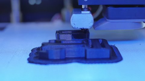 3D Printer frontal closeup printing a black piece