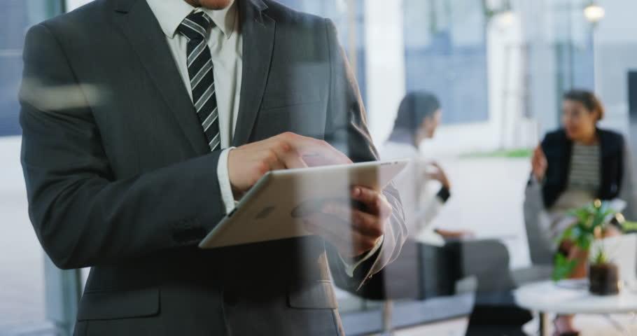 Smiling businessman using digital tablet in office 4k   Shutterstock HD Video #20399671