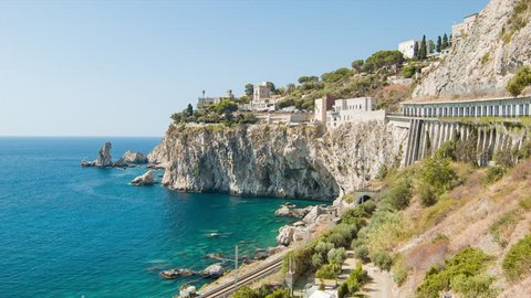 Taormina Sicily Coast Against Steep Cliffs with Passing Train on Railroad Against Blue Mediterranean Sea Water on a Sunny Summers Day in Italy