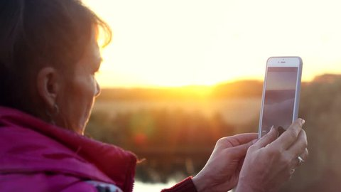 Mature woman in age using a phone in the mountains during sunset. 3840x2160