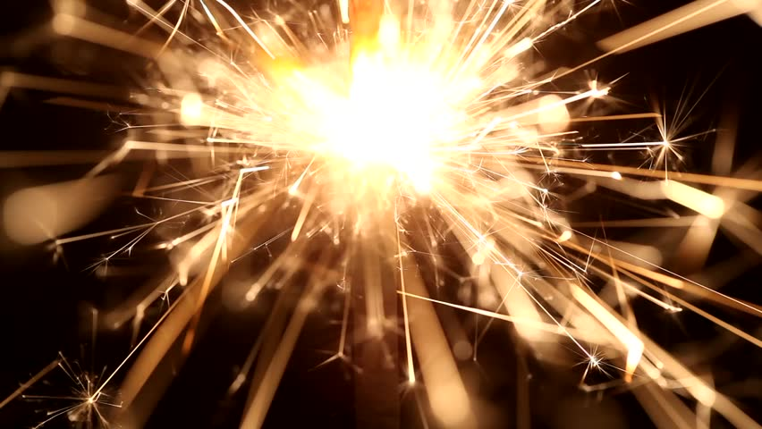 Macro of burning sparklers with a dark background.