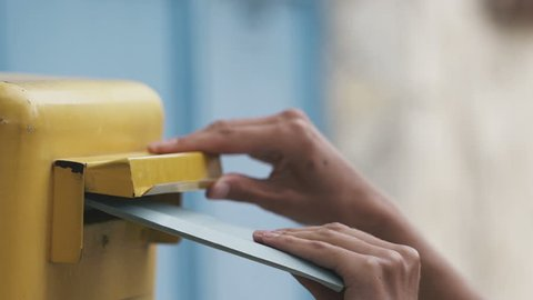Woman is sending a blue letter into a yellow letterbox. Slow motion 120 fps