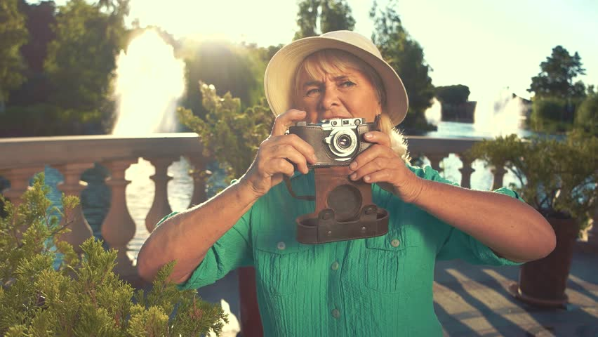 Senior woman with photo camera. Mature lady in summer hat. Interest and inspiration. Models are too shy.