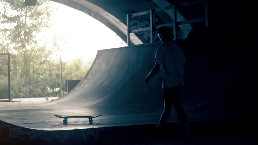 Skateboarder walk with skate HD video slow motion on ramp skateboard park. Urban extreme sport lifestyle
