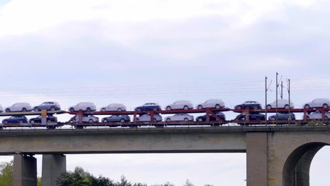 cargo train loaded with brand new cars for export shipping rolling over a bridge