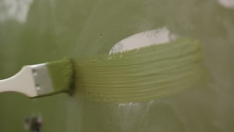 closeup of painting house wall with paintbrush in green color horizontal brushstroke