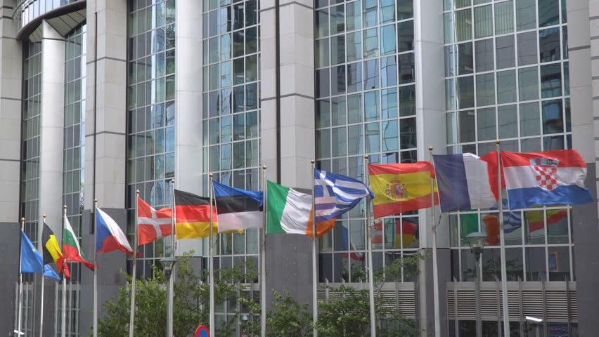 All European Union or EU countries national flags (Germany, France, Czech republic, Denmark, Italy etc) as also blue Europe flag, waving in front of euro parliament building in Brussels city, Belgium.