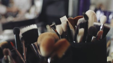 Set of brushes for make-up on table in dressing room. Fashion industry. Fashion show backstage.