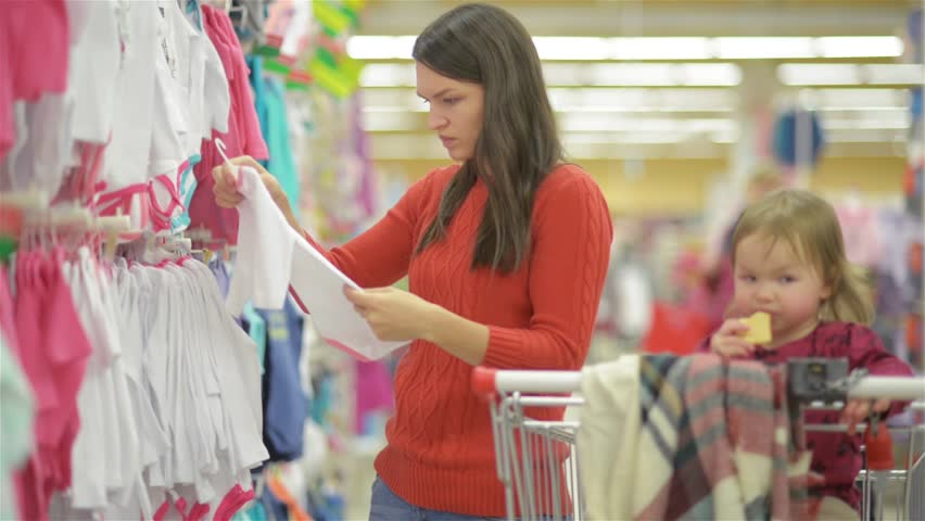 Attractive young mother shopping for childrens clothes in a retail clothing store viewing items on a rack, beautiful woman chooses baby clothes in shop, woman shopping in a supermarket | Shutterstock HD Video #20534806
