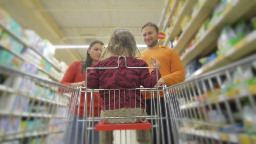 Beautiful young parents and their cute little daughter are smiling while choosing food in the supermarket. Girl is sitting in the shopping cart | Shutterstock HD Video #20534815